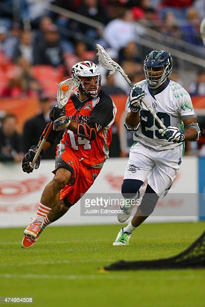 Justin Pennington of the Denver Outlaws in action against the against Mark McNeill of the Chesapeake Bayhawks at Sports Authority Field at Mile High...