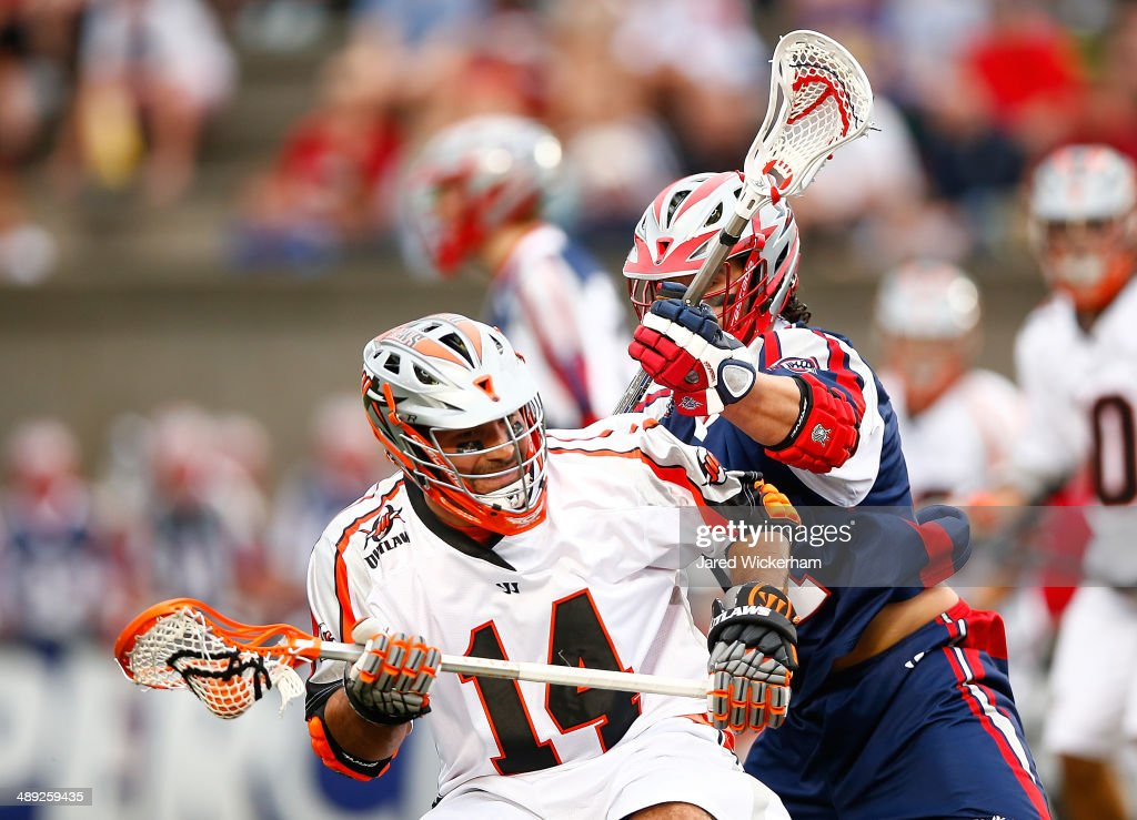 Justin Pennington #14 of the Denver Outlaws is defended by Matt Smalley #14 of the Boston Cannons in the first half at Harvard Stadium on May 10, 2014 in Boston, Massachusetts.