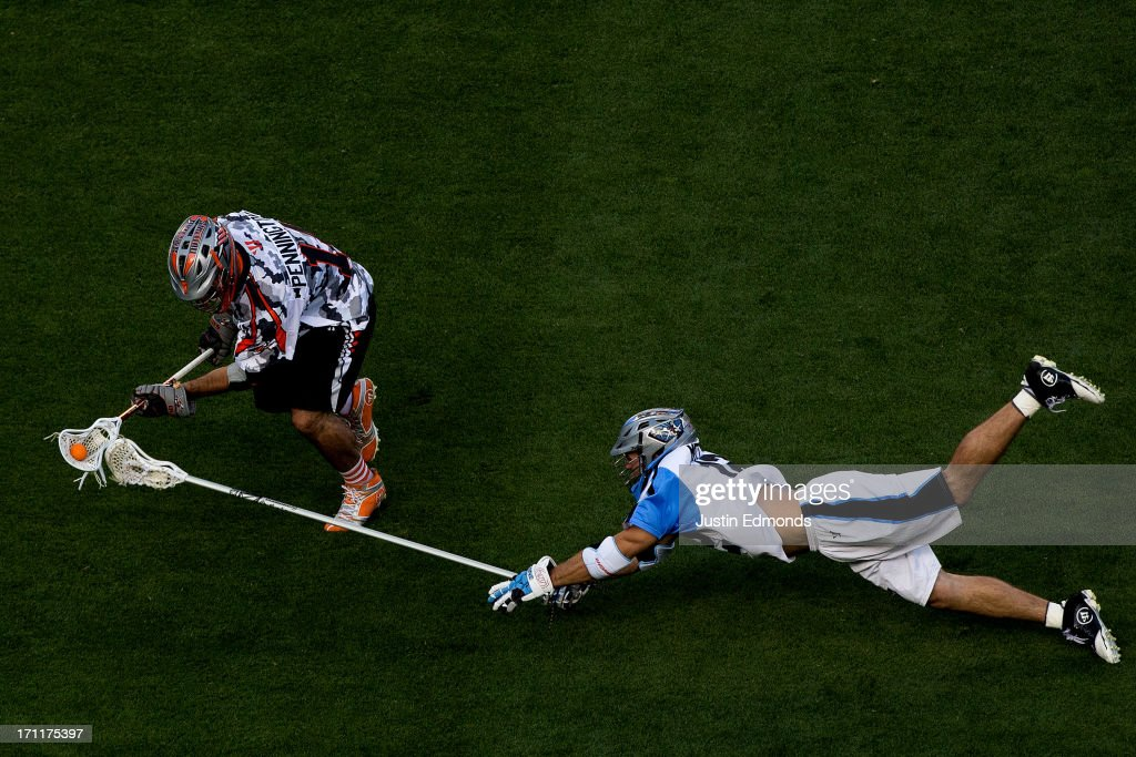 Justin Pennington #14 of the Denver Outlaws scoops up a ground ball as Ray Megill #12 of the Ohio Machine makes a diving effort during the second quarter at Sports Authority Field at Mile High on June 22, 2013 in Denver, Colorado.