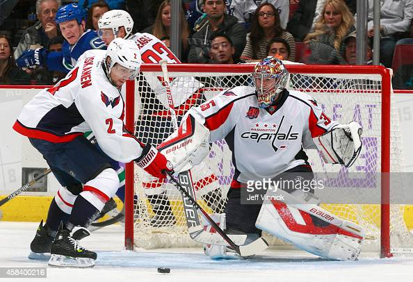 Justin Peters looks on as teammate Matt Niskanen of the Washington Capitals watches a rebound during their NHL game against the Vancouver Canucks at...