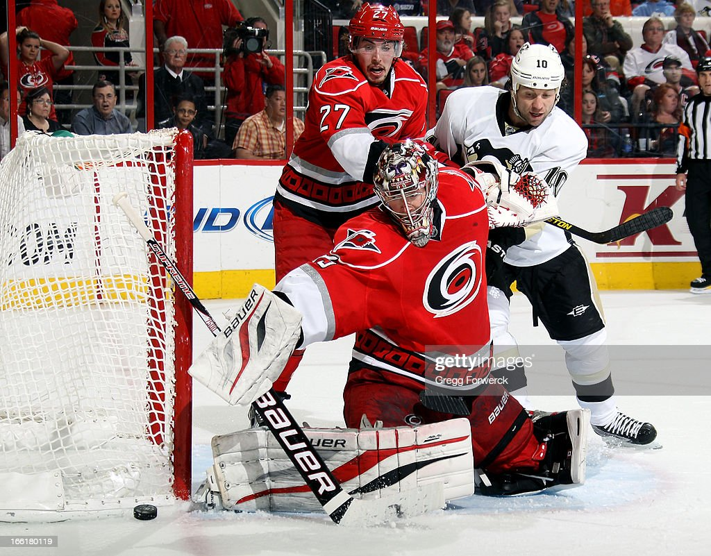 Justin Peters #27 of the Carolina Hurricanes and <a gi-track='captionPersonalityLinkClicked' href=/galleries/search?phrase=Brenden+Morrow&family=editorial&specificpeople=202256 ng-click='$event.stopPropagation()'>Brenden Morrow</a> #10 of the Pittsburgh Penguins battle for position in the crease as Justin Peters #35 makes a pad save during their NHL game at PNC Arena on April 9, 2013 in Raleigh, North Carolina.