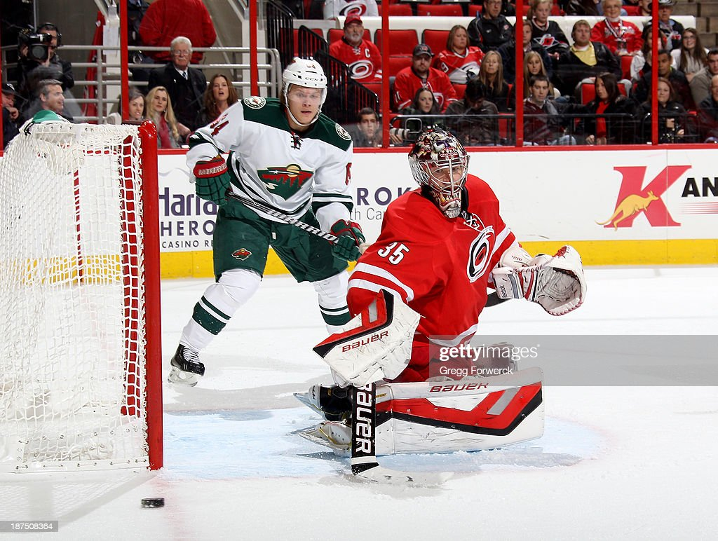 Justin Peters #35 of the Carolina Hurricanes deflects the puck and defends the net against Mikael Granlund #64 of the Minnesota Wild during their NHL game at PNC Arena on November 9, 2013 in Raleigh, North Carolina.