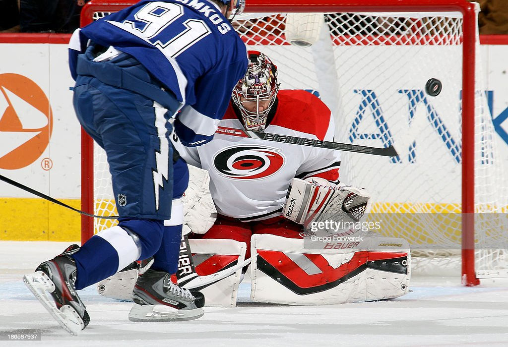 Justin Peters #35 of the Carolina Hurricanes deflects the puck wide of the net after blocking a shot from Steven Stamkos #91 of the Tampa Bay Lightning during their NHL game at PNC Arena on November1, 2013 in Raleigh, North Carolina.
