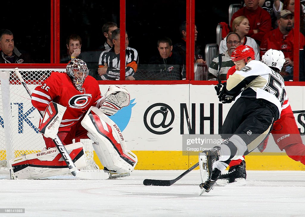 Justin Peters #35 of the Carolina Hurricanes eyes the puck following a shot from Kris Letang #58 of the Pittsburgh Penguins as Tim Gleason #6 closes in to defend him during their NHL game at PNC Arena on October 28, 2013 in Raleigh, North Carolina.