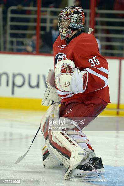 Justin Peters of the Carolina Hurricanes looks on against the Pittsburgh Penguins at PNC Arena on December 27 2013 in Raleigh North Carolina The...