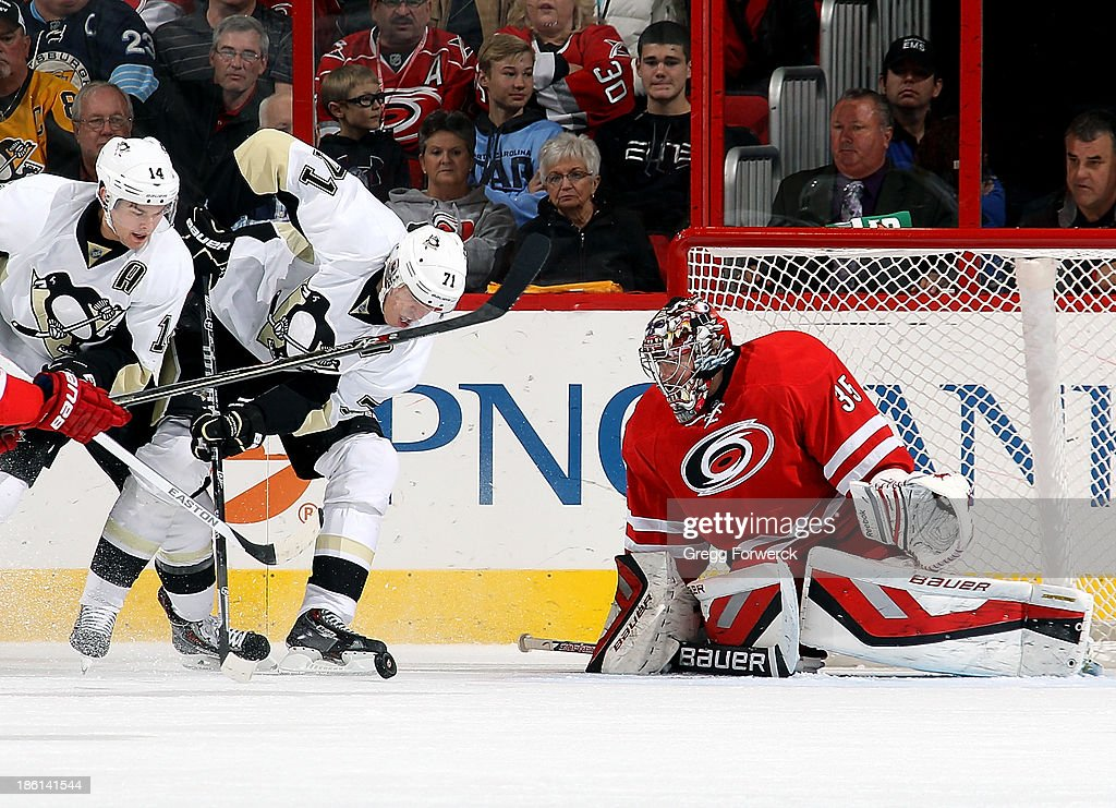 Justin Peters #35 of the Carolina Hurricanes protects the goal as the puck rolls toward the crease at the skates of Chris Kunitz #14 and Evgeni Malkin #71 of the Pittsburgh Penguins during their NHL game at PNC Arena on October 28, 2013 in Raleigh, North Carolina.