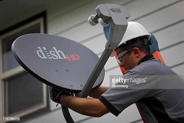 Justin Preziosi field service specialist for Dish Network Corp installs a satellite television system at a residence in Denver Colorado US on Tuesday...