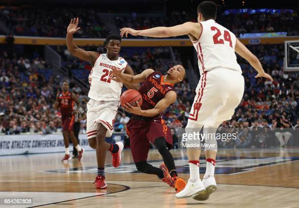 Justin Robinson of the Virginia Tech Hokies drives against Khalil Iverson and Bronson Koenig of the Wisconsin Badgers in the first half during the...