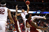 Justin Robinson of the Virginia Tech Hokies puts up a shot as he is fouled by Malik Beasley and Jarquez Smith of the Florida State Seminoles during...