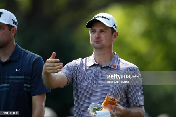 Justin Rose eats a sandwich as he walks the 18th hole during the second round of the PGA Championship on August 11 2017 at Quail Hollow Club in...