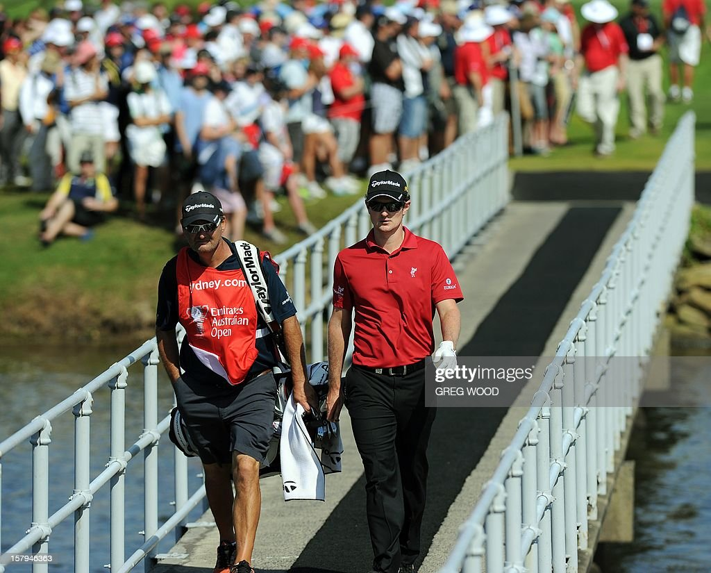 Justin Rose from England (R) walks across a bridge on the 17th fairway in front of a large following gallery during round three of the Australian Open golf at The Lakes course in Sydney on December 8, 2012. IMAGE STRICTLY RESTRICTED TO EDITORIAL USE - STRICTLY NO COMMERCIAL USE AFP PHOTO / Greg WOOD