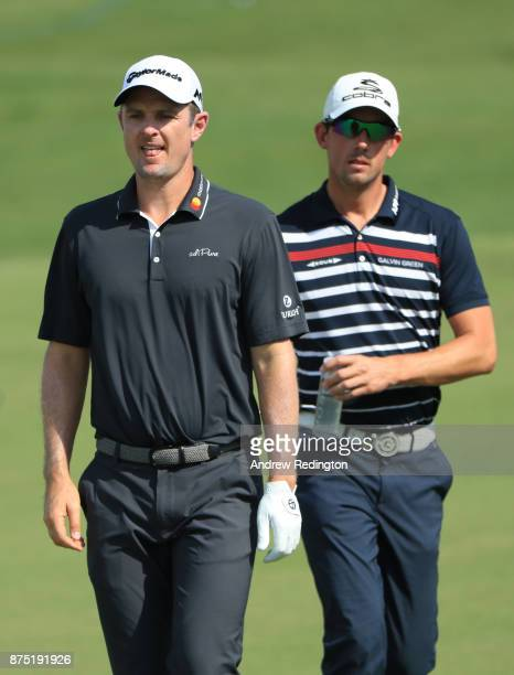 Justin Rose of England and Alexander Bjork of Sweden walk down the 1st hole during the second round of the DP World Tour Championship at Jumeirah...