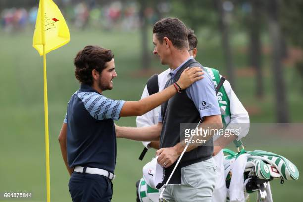 Justin Rose of England and amatuer Toto Gana of Chile walk off the seventh hole after play was suspended during a practice round prior to the start...