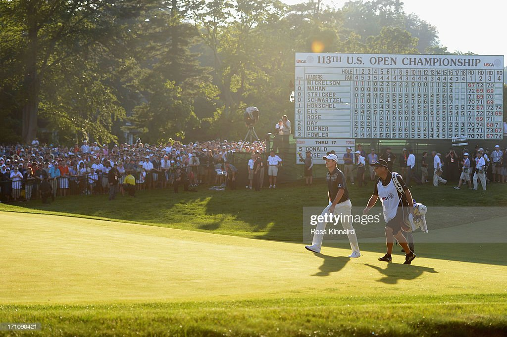 Justin Rose of England and caddie Mark Fulcher walk up to the 18th green during the final round of the 113th U.S. Open at Merion Golf Club on June 16, 2013 in Ardmore, Pennsylvania.