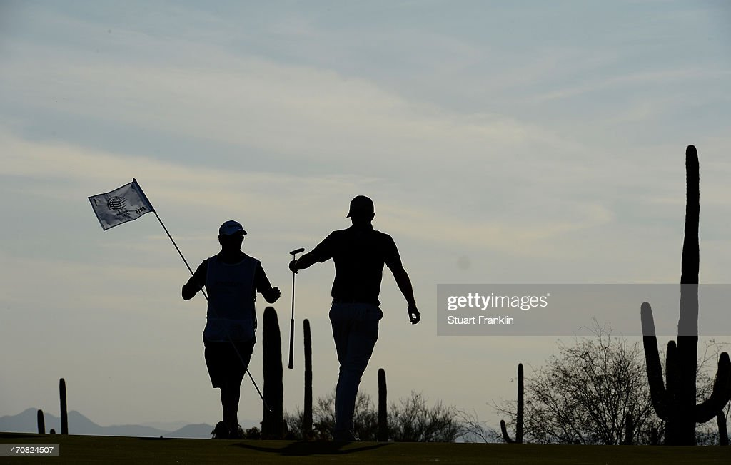 Justin Rose of England and caddie on the first play off hole during the second round of the World Golf Championships - Accenture Match Play Championship at The Golf Club at Dove Mountain on February 20, 2014 in Marana, Arizona.