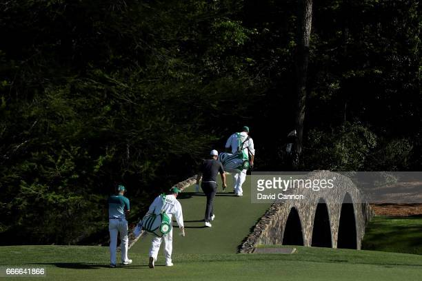 Justin Rose of England and Sergio Garcia of Spain cross the Hogan Bridge with their caddies during the final round of the 2017 Masters Tournament at...