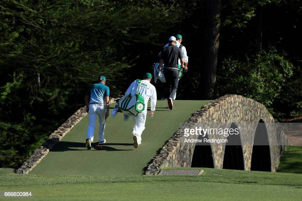 Justin Rose of England and Sergio Garcia of Spain walk over the Hogan Bridge with their caddies Mark Fulcher and Glen Murray during the final round...