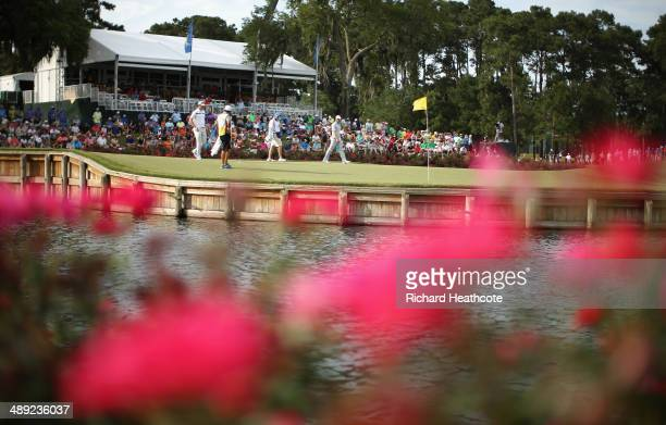 Justin Rose of England and Sergio Garcia of Spain walk to the 17th greenb with their caddies during the third round of THE PLAYERS Championship on...