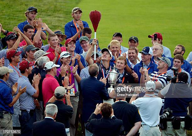 Justin Rose of England celebrates with the US Open trophy admist a group of people while holding a wicker basket flagstick after winning the 113th US...