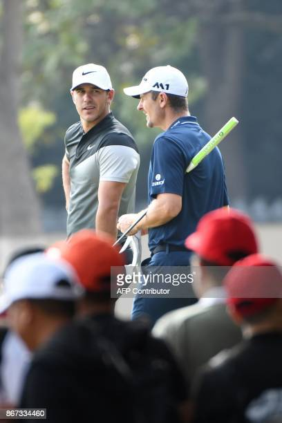 Justin Rose of England chats with Brooks Koepka of the US as they wait to tee off during the third round of the WGCHSBC Champions at the Sheshan...