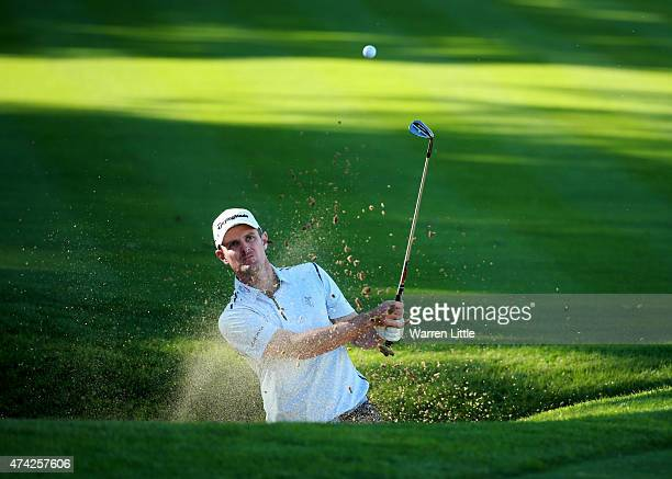 Justin Rose of England hits from a greenside bunker on the 18th hole during day 1 of the BMW PGA Championship at Wentworth on May 21 2015 in Virginia...