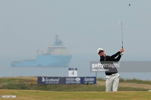 Justin Rose of England hits his approach shot on the 16th hole during the third round of the 2014 Aberdeen Asset Management Scottish Open at Royal...