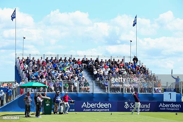 Justin Rose of England hits his tee shot on the first hole as a grandstand of fans look on during the first round of the Aberdeen Asset Management...
