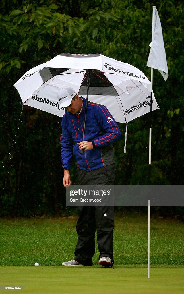 Justin Rose of England holds an umbrella while preparing to putt on the first green during the Final Round of the BMW Championship at Conway Farms Golf Club on September 15, 2013 in Lake Forest, Illinois.
