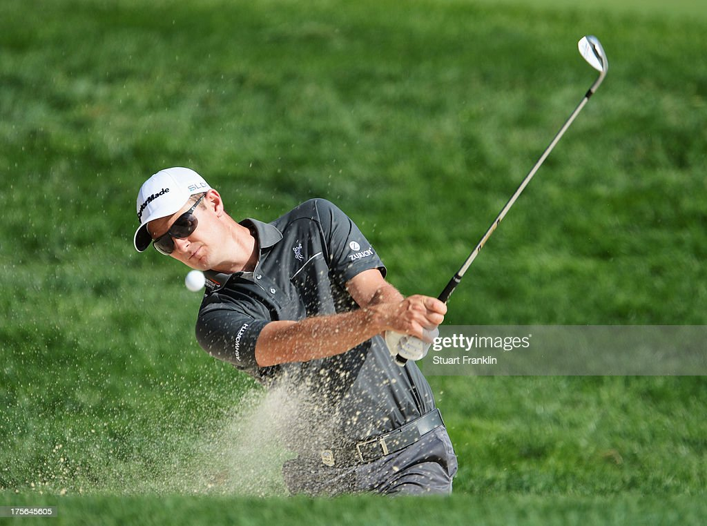 Justin Rose of England plays a bunker shot during a practice round prior to the start of the 95th PGA Championship at Oak Hill Country Club on August 5, 2013 in Rochester, New York.
