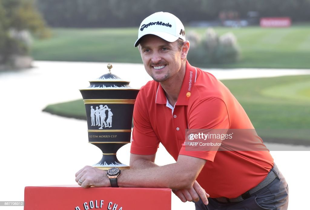 Justin Rose of England poses with his trophy after he stormed back from eight shots behind overnight to win the 9.75 million USD WGC-HSBC Champions by two strokes in a thrilling finale at the Sheshan International golf club in Shanghai on October 29, 2017. /