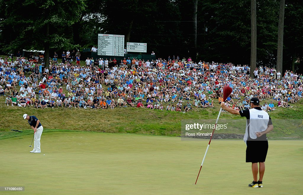 Justin Rose of England putts on the ninth green as caddie Mark Fulcher holds the wicker basket flagstick during the final round of the 113th U.S. Open at Merion Golf Club on June 16, 2013 in Ardmore, Pennsylvania.