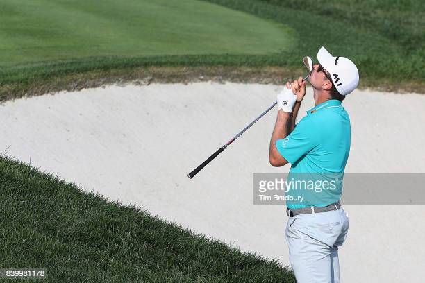 Justin Rose of England reacts after hitting from a greenside bunker on the 18th green during the final round of The Northern Trust at Glen Oaks Club...