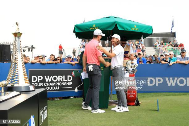 Justin Rose of England shakes hands with Tommy Fleetwood of England on the 1st tee during the first round of the DP World Tour Championship at...