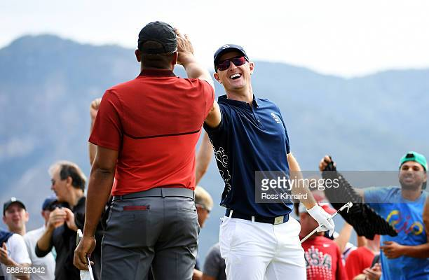 Justin Rose of Great Britain celebrates with Jhonattan Vegas of Venezuela after hitting a hole in one on the fourth hole during the first round of...