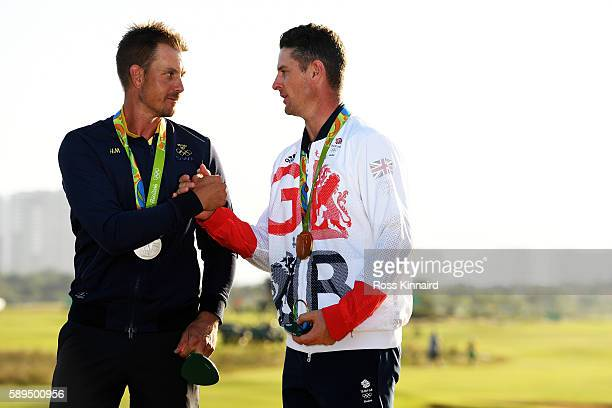 Justin Rose of Great Britain celebrates with the gold medal and Henrik Stenson of Sweden silver medal after the final round of men's golf on Day 9 of...