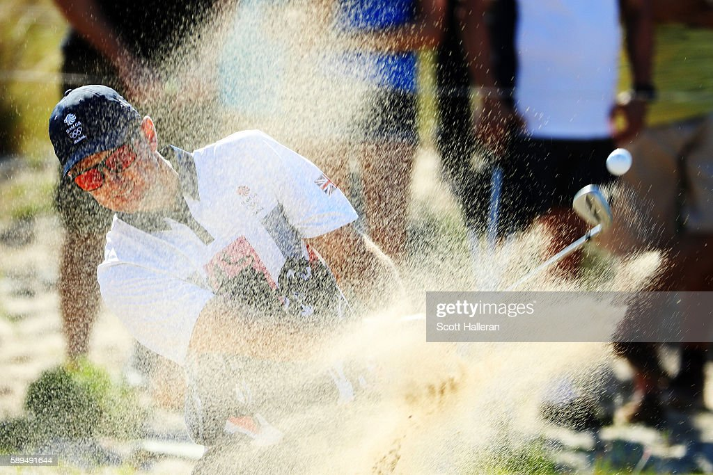 Justin Rose of Great Britain plays a shot from a bunker on the 14th hole during the final round of men's golf on Day 9 of the Rio 2016 Olympic Games...