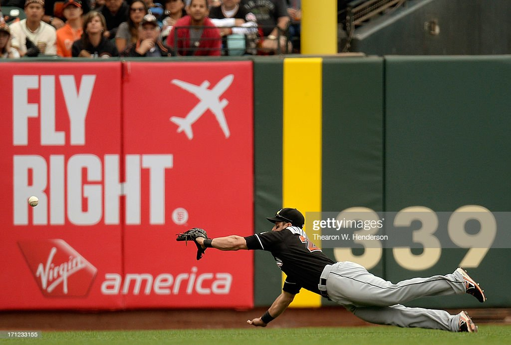 Justin Ruggiano #20 of the Miami Marlins dives but is unable to come up with the ball that goes for a triple off the bat of Tony Abreu #10 of the San Francisco Giants in the sixth inning at AT&T Park on June 23, 2013 in San Francisco, California.