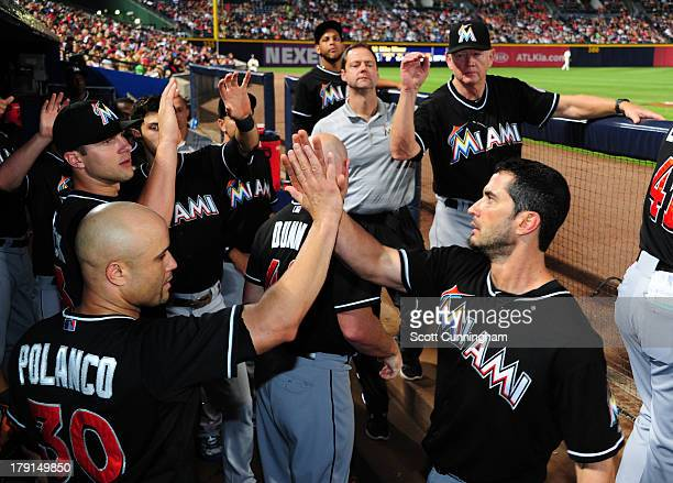 Justin Ruggiano of the Miami Marlins is congratulated by Placido Polanco after scoring a seventh inning run against the Atlanta Braves at Turner...