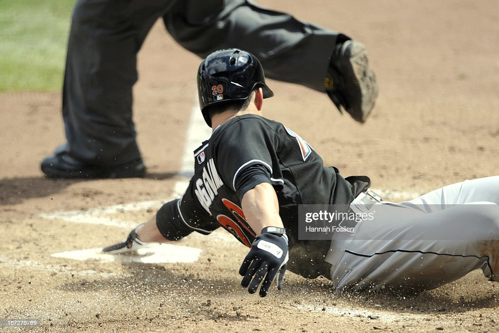 <a gi-track='captionPersonalityLinkClicked' href=/galleries/search?phrase=Justin+Ruggiano&family=editorial&specificpeople=4536828 ng-click='$event.stopPropagation()'>Justin Ruggiano</a> #20 of the Miami Marlins touches home plate as he slides safely to score against the Minnesota Twins during the fourth inning of the first game of a doubleheader on April 23, 2013 at Target Field in Minneapolis, Minnesota.