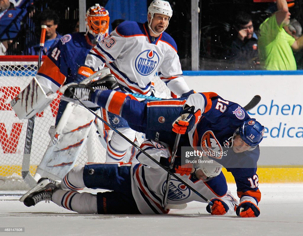 Justin Schultz #19 of the Edmonton Oilers and Josh Bailey #12 of the New York Islanders hit the ice during the second period at the Nassau Veterans Memorial Coliseum on February 10, 2015 in Uniondale, New York.