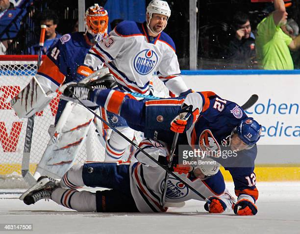Justin Schultz of the Edmonton Oilers and Josh Bailey of the New York Islanders hit the ice during the second period at the Nassau Veterans Memorial...