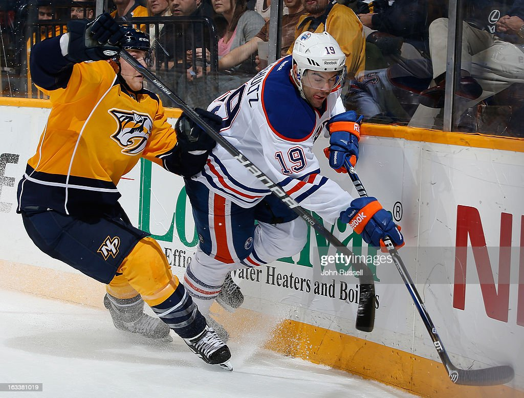 <a gi-track='captionPersonalityLinkClicked' href=/galleries/search?phrase=Justin+Schultz&family=editorial&specificpeople=5370958 ng-click='$event.stopPropagation()'>Justin Schultz</a> #19 of the Edmonton Oilers battles along the boards against Colin Wilson #33 of the Nashville Predators during an NHL game at the Bridgestone Arena on March 8, 2013 in Nashville, Tennessee.