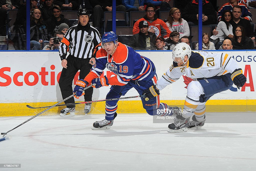 Justin Schultz #19 of the Edmonton Oilers battles for the puck against Henrik Tallinder #20 of the Buffalo Sabres on March 20, 2014 at Rexall Place in Edmonton, Alberta, Canada.