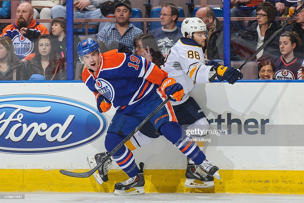Justin Schultz #19 of the Edmonton Oilers collides with Cory Conacher #88 of the Buffalo Sabres during an NHL game at Rexall Place on March 20, 2014 in Edmonton, Alberta, Canada.