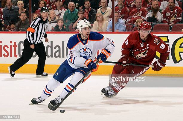 Justin Schultz of the Edmonton Oilers skates with the puck ahead of Shane Doan of the Phoenix Coyotes during the third period at Jobingcom Arena on...