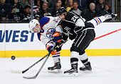 Justin Schultz of the Edmonton Oilers takes an off balance shot while defended by Slava Voynov of the Los Angeles Kings in the first period at...