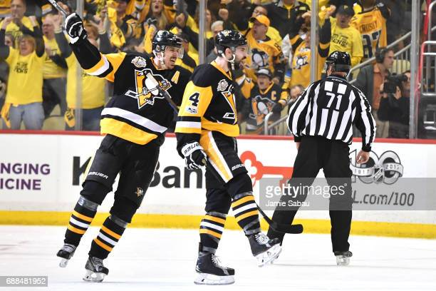 Justin Schultz of the Pittsburgh Penguins celebrates with his teammate Evgeni Malkin after scoring a goal against Craig Anderson of the Ottawa...