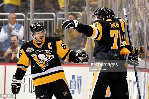 Justin Schultz of the Pittsburgh Penguins celebrates with his teammates Sidney Crosby and Evgeni Malkin after scoring a goal against Craig Anderson...