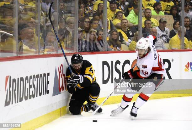 Justin Schultz of the Pittsburgh Penguins kneels on the ice in pain after being checked by Mike Hoffman of the Ottawa Senators during the first...