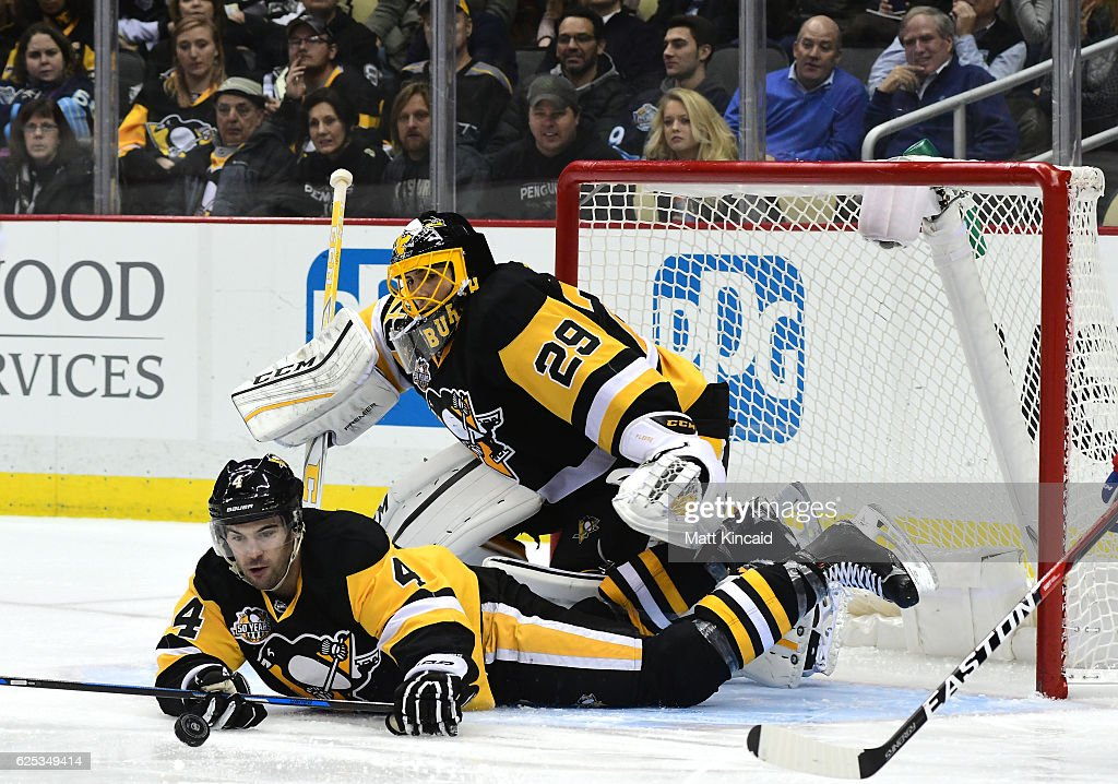 Justin Schultz #4 of the Pittsburgh Penguins reaches for the puck while laying on the ice against the New York Rangers at PPG PAINTS Arena on November 21, 2016 in Pittsburgh, Pennsylvania.